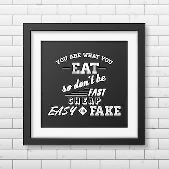 당신은 당신이 먹는 것이므로 빠르고 쉽게 싸거나 가짜가 아닙니다-벽돌 벽에 인쇄상의 현실적인 사각 검은 색 프레임을 인용하십시오.
