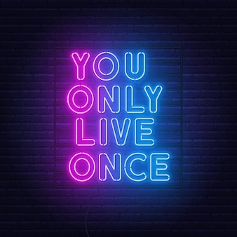 You only live once neon lettering on a brick wall.