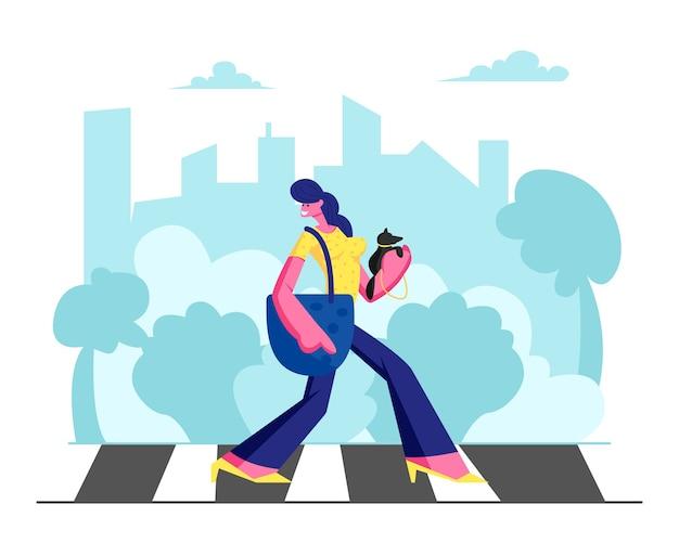 Молодая очаровательная женщина в модном платье с маленькой собачкой в руках гуляет по пешеходному переходу в большом оживленном мегаполисе, образ жизни девушки-горожанина, свободное время, движение