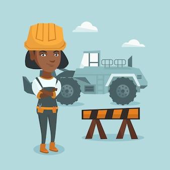 Молодой афро-американский строитель со скрещенными руками.