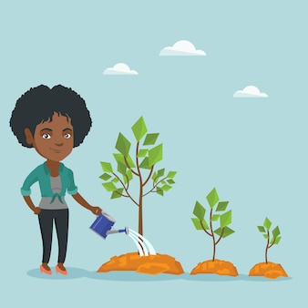 Young african businesswoman watering trees.