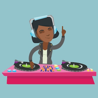 Young african dj mixing music on turntables.