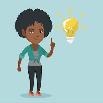Молодой африканский студент указывая на лампочку идеи.