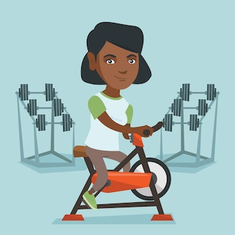 Young african woman riding stationary bicycle.