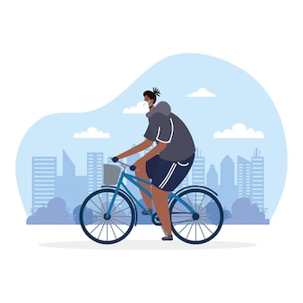 医療マスクを身に着けている若いアフロ男乗馬自転車