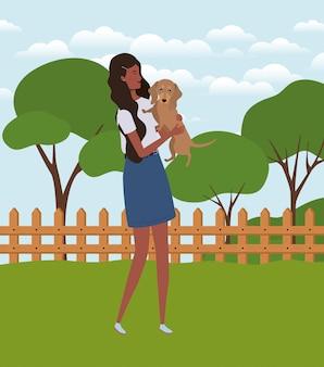 Молодая афро женщина поднимая милую собаку в поле