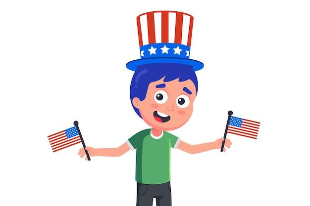 Молодой американец в шляпе и с флагами празднует день независимости.
