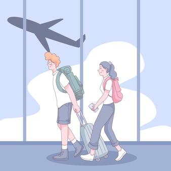 젊은 배낭 부부는 만화 캐릭터로 공항에서 수하물을 끌고 있습니다.