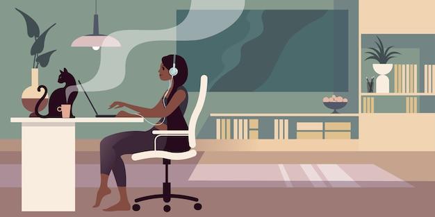 Молодая босая брюнетка с наушниками сидит за столом и работает на ноутбуке.