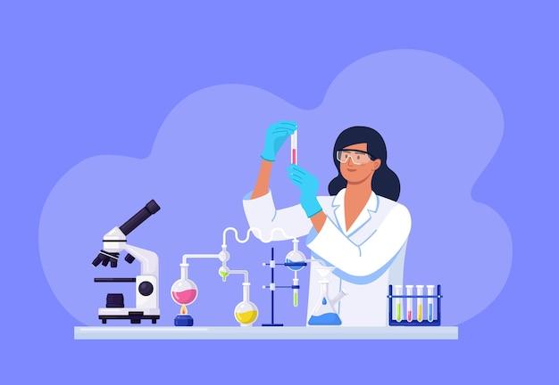 Молодая красивая женщина-химик с колбами с жидкостью в руке. девушка-ученый экспериментирует с оборудованием для открытия вакцины. девушка работает над разработкой противовирусного лечения