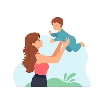 上げられた手で男の子を保持している若い美しい女性の母親