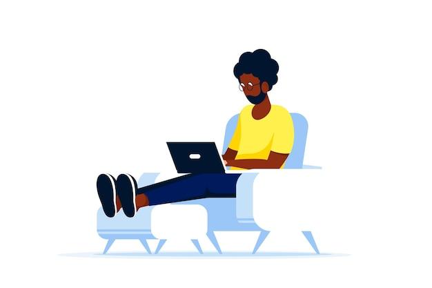 Молодой черный человек сидит в кресле и работает на компьютере. удаленная работа, домашний офис, концепция самоизоляции. плоский стиль.
