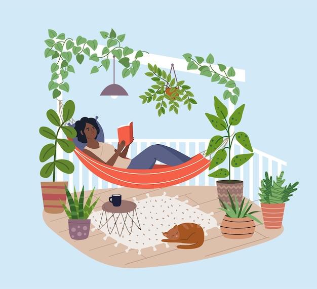 Молодая темнокожая женщина расслабляется в гамаке на террасе, читая книгу