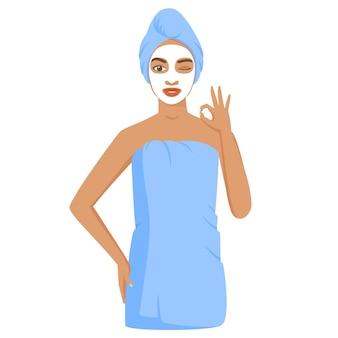 목욕이나 샤워 후 수건에 싸인 젊은 흑인 여성 화장용 점토 또는 시트 마스크를 사용하는 여성