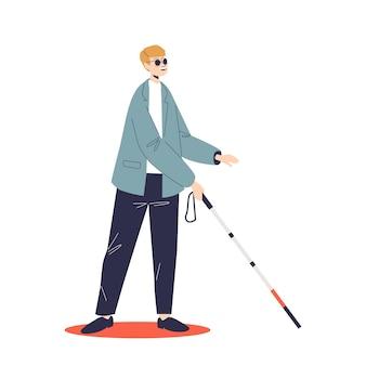 선글라스를 쓴 젊은 맹인은 지팡이로 움직입니다. 장애 및 시력 질환이 있는 남성