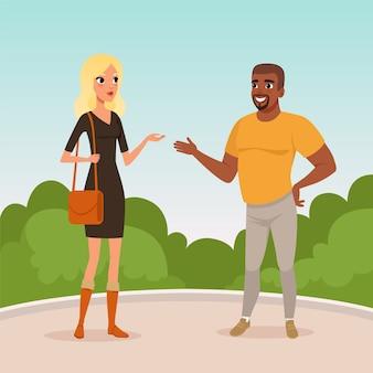 若いブロンドの女性とひげを生やしたアフリカ系アメリカ人の男性が公園に立って会話をしています