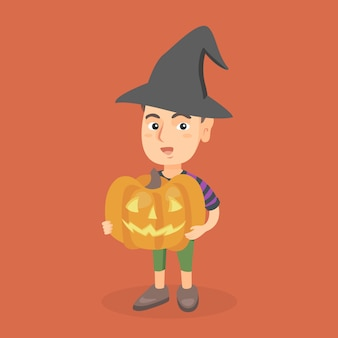 Young boy holding a carved pumpkin for halloween.