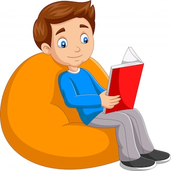 Young boy reading a book sitting on big pillow