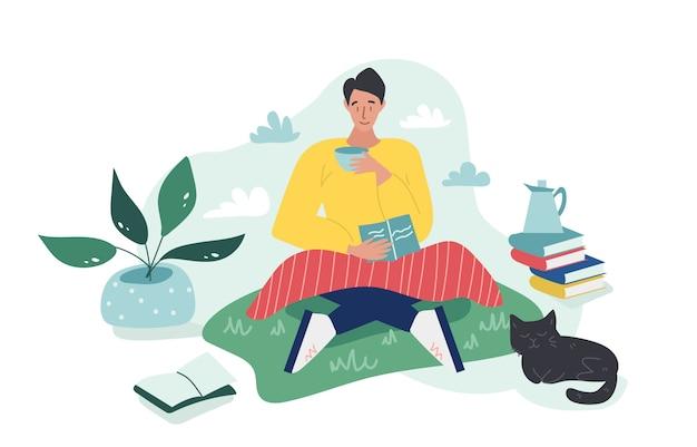 Молодой мальчик сидя на траве с шотландкой и читает книгу пока выпивающ чашку чаю или кофе в пасмурном дне. черный кот спит неподалеку. цветной мультфильм плоской иллюстрации.