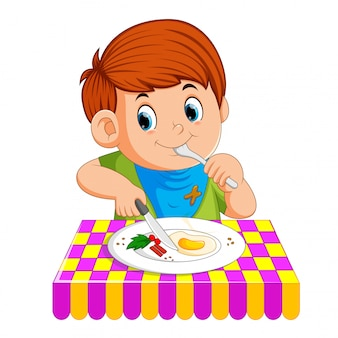 A young boy sitting while enjoy having breakfast
