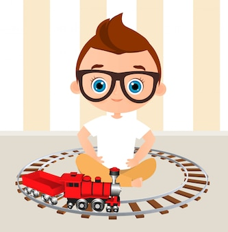Young boy with glasses and toy train. boy playing with train.