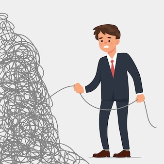 Young businessman holds the end of a very tangled rope