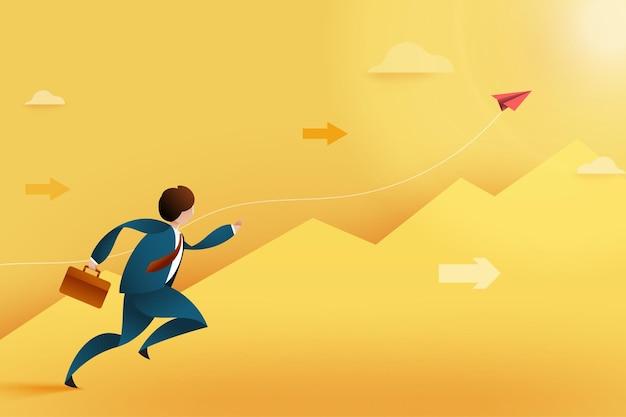 Молодой бизнесмен, бегущий вперед к поднимающемуся красный бумажный самолетик