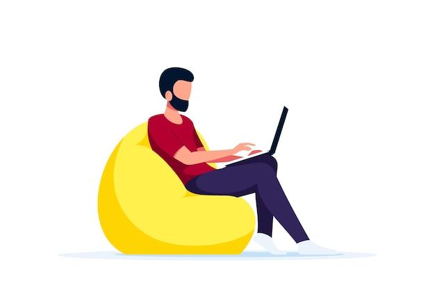 椅子のバッグに座って、コンピューターで作業している若い白人男性。在宅勤務、ホームオフィス、自己隔離の概念。フラットスタイル。