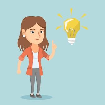 Молодой кавказский студент указывая на лампочку идеи