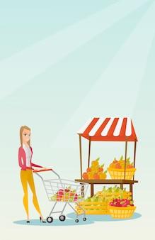 Young caucasian woman pushing a supermarket cart.