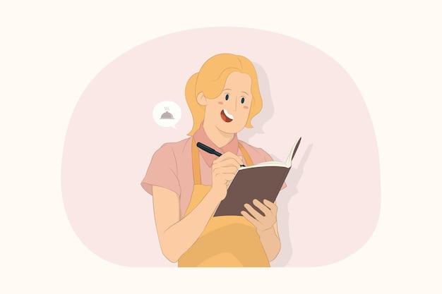 젊은 셰프 쿡 베이커 여성은 노트북 개념으로 메모를 하는 요리책에 조리법을 기록합니다.