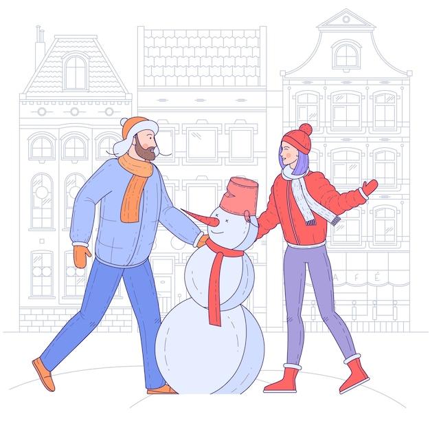 若いカップルは、旧市街の都会の背景で雪だるまを作っています。 Premiumベクター