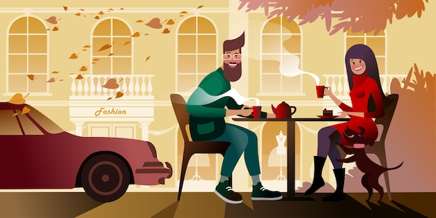 Young couple drinking tea on the autumn terrace of the city cafe. city street scene.