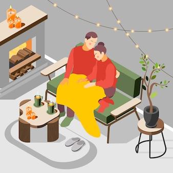 コーヒーの等角投影図とソファの上の格子縞の下に座ってヒュッゲデンマークのライフスタイルを楽しんでいる若いカップル