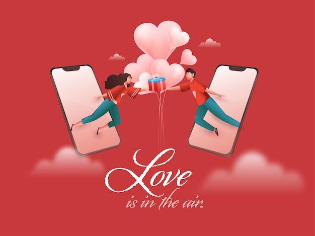Молодая пара держит подарочную коробку с воздушными шарами в форме сердца через смартфон