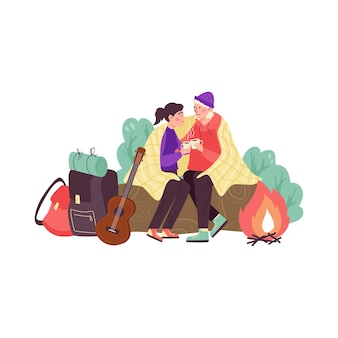 Young couple man and woman together sitting near bonfire camping outdoor nature