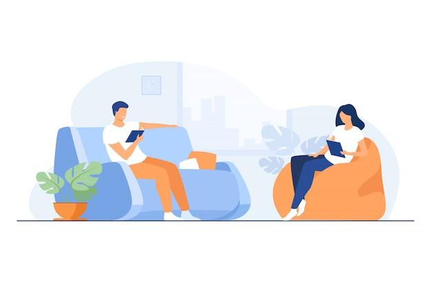 若いカップルがリビングルームで本を読んで