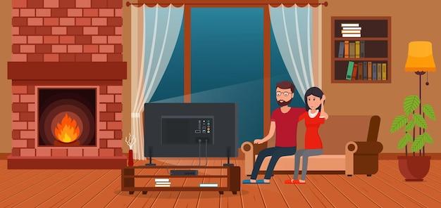 暖炉のそばでテレビを見ながらソファに座っている若いカップル。現代的なリビングルームのインテリア。