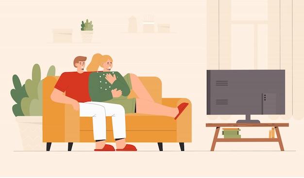 Молодые пары сидя на софе смотря новости тв дома в уютной комнате. шокирующий контент, негативные новости.