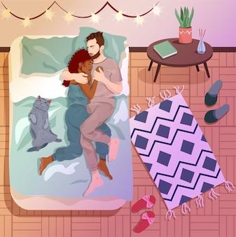 猫と居心地の良いアパートで寝ている若いカップル。強い思いやりのある関係と愛着のコンセプト。