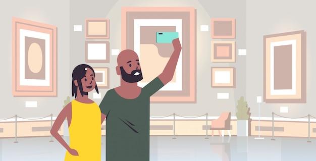 現代アートギャラリーミュージアムインテリアポートレート水平方向のスマートフォンカメラ男性女性訪問者でselfie写真を撮る若いカップル