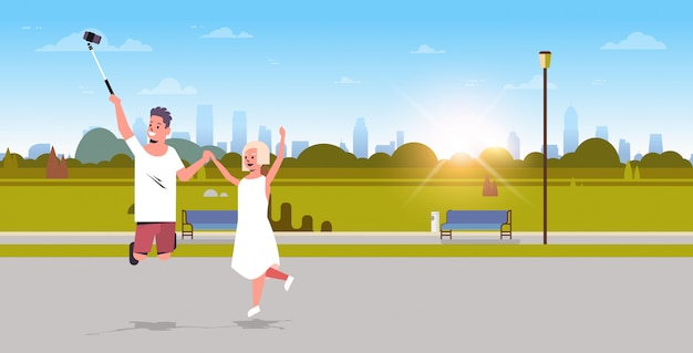 スマートフォンのカメラで写真を撮るselfieスティックを使用して若いカップルジャンプして楽しい女性都市女性都市公園日の出風景背景全長水平