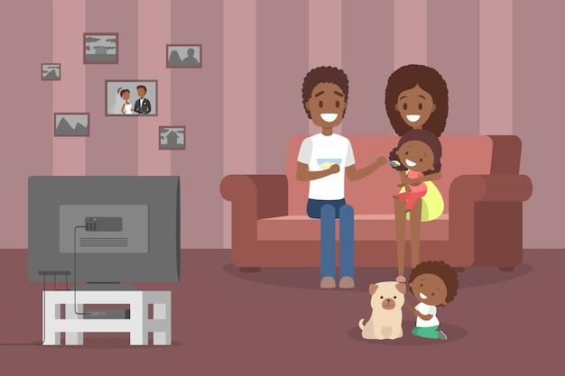 リビングルームでテレビを見て一緒に時間を過ごす若いかわいい家族。父と母は自分の小さな娘を養います。犬と遊ぶ少年。図