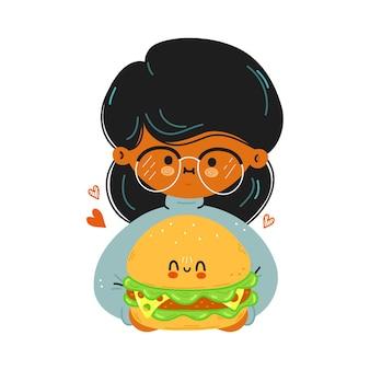 若いかわいい面白い女の子は、ハンバーガーを手に持っています