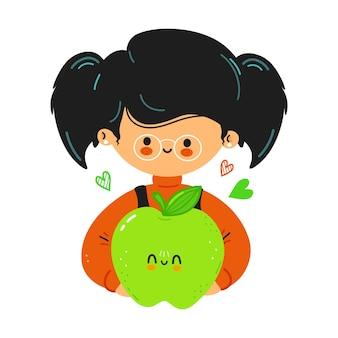 젊고 귀여운 재미있는 어린 소녀가 녹색 사과를 손에 들고 있습니다.