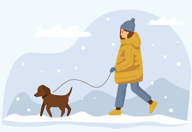 A young cute woman in a warm jacket walks her dog in winter.
