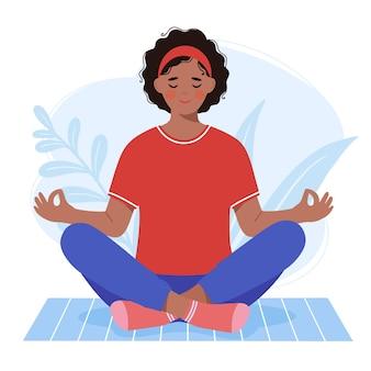 若い浅黒い肌の女性は、ヨガマットに座って瞑想します。