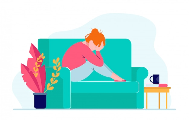 Молодая подавленная женщина сидя на софе и держа голову