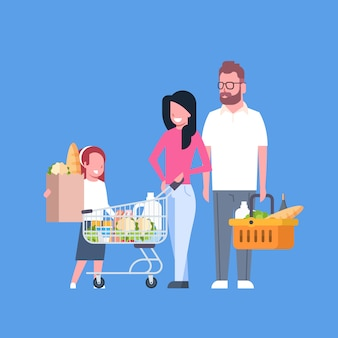 Young family shopping holding paper bag, cart and basket full of grocery products