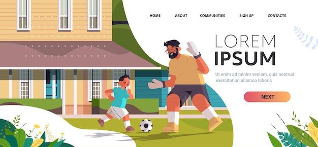 裏庭の芝生で息子とサッカーをしている若い父親の子育ての父性の概念お父さんは彼の子供と一緒に時間を過ごしています